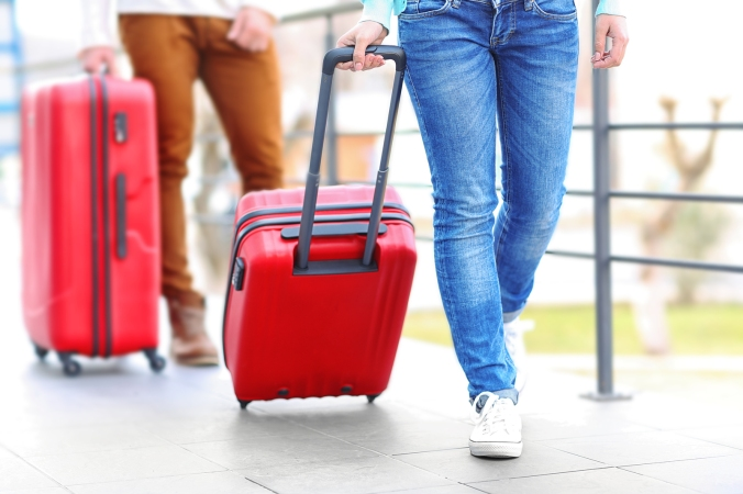 Couple rolling large red suitcases, close up