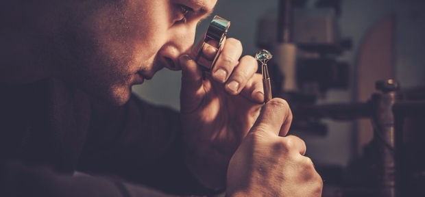 Jeweler looking at the ring through microscope in a workshop.