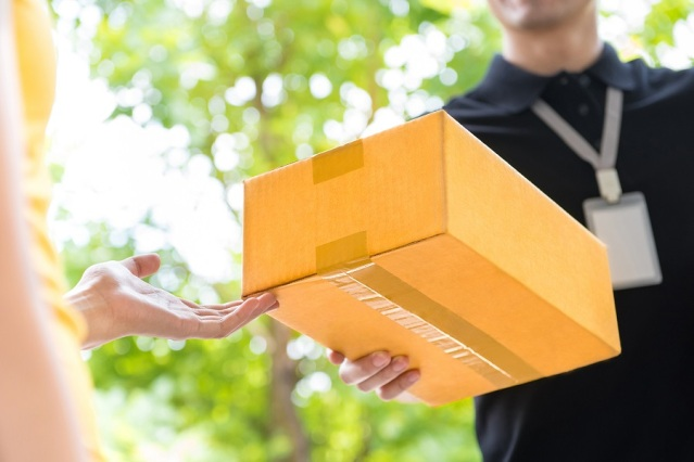 Delivery man delivering package to customer close up at hand and box