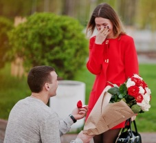 Marriage Proposal. Man With Boquet Of Flowers Kneeling And Give